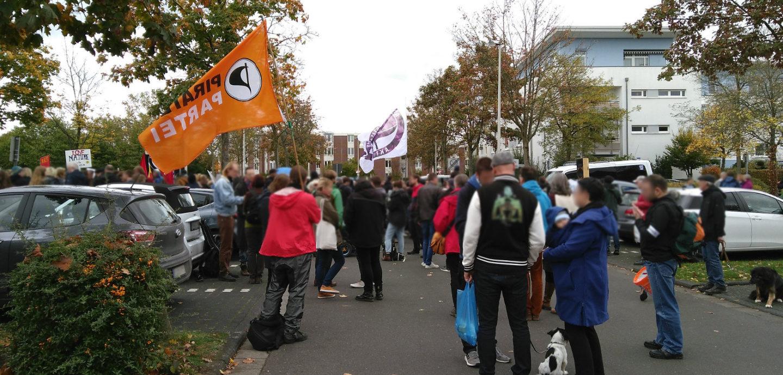 Menschenmasse mit u.a. Piratenparteiflagge vor dem Ortsteilzentrum